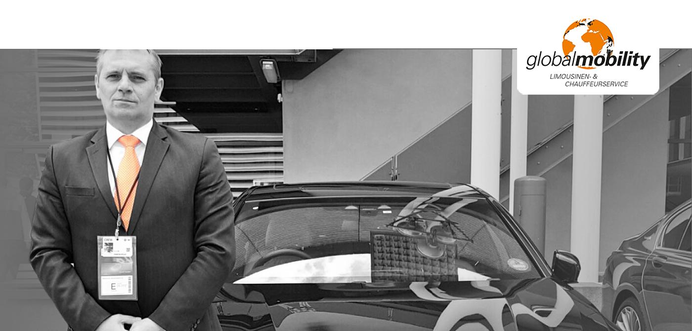 Freundlicher Fahrer von Glbal Mobility vor einer schwarzen Limousine