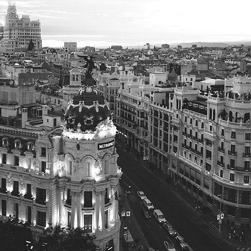 Metropolisgebäude und belebte Straße am Abend